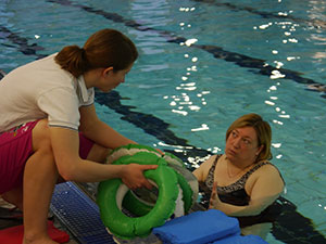 instructor passing woman swimming equipment South West Yorkshire Partnership NHS Foundation Trust